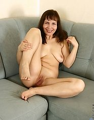 Long haired cougar spreads her mature pink hole on the sofa while completely naked