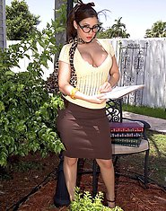 Busty brunette poses outdoors
