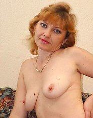 Horny mature redhead takes off her nylons on a couch