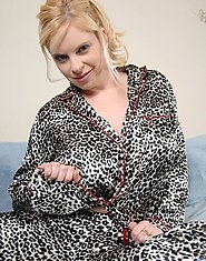 Lovely blonde woman in silky leopard pajamas poses and teases us in bed
