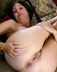Enticing mature mom spreads her pussy and dips her fingers inside making herself wet on the couch